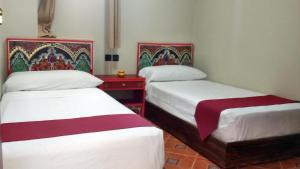 A bed or beds in a room at Hotel Maram