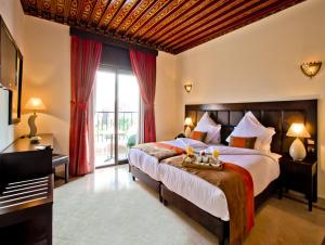 A bed or beds in a room at Hotel Lawrence d'Arabie