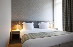 A bed or beds in a room at Mercure Brides Les Bains Grand Hôtel des Thermes