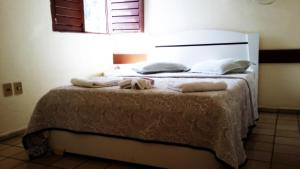 A bed or beds in a room at Escuna Praia Hotel