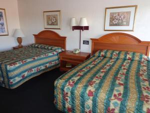 A bed or beds in a room at Red Carpet Inn Daytona Beach