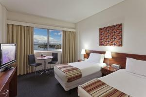 A bed or beds in a room at Macleay Hotel
