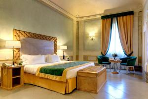 A bed or beds in a room at Villa Tolomei Hotel & Resort