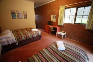 A bed or beds in a room at The Harrietville Snowline Hotel