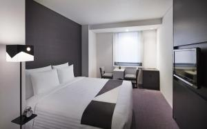 A bed or beds in a room at Courtyard by Marriott Tokyo Station