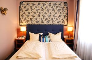 A bed or beds in a room at Historik Hotel Goldener Hirsch Rothenburg