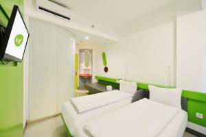 A bed or beds in a room at POP! Hotel Malioboro - Yogyakarta