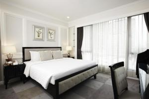 A bed or beds in a room at Cape House Langsuan Hotel