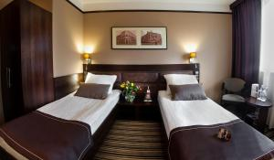 A bed or beds in a room at Park Hotel Diament Katowice