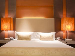A bed or beds in a room at The Raintree, Anna Salai