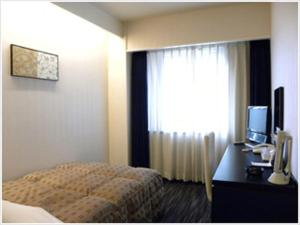 A bed or beds in a room at Hotel North City