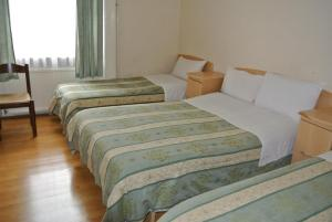 A bed or beds in a room at The Belgrove Hotel
