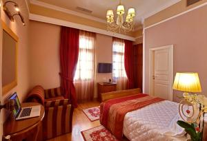 A bed or beds in a room at Aetoma Hotel
