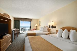 A bed or beds in a room at Days Inn by Wyndham Daytona Oceanfront