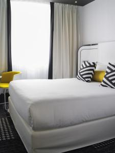 A bed or beds in a room at Hotel Ekta Champs Elysées