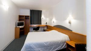 A bed or beds in a room at Hotel First Rodez