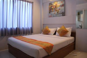 A bed or beds in a room at New Yangon Hotel