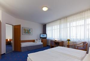 A bed or beds in a room at Kim Hotel Dresden