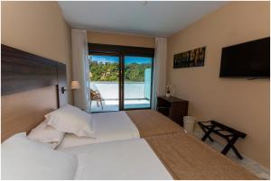 A bed or beds in a room at Hotel Abetos del Maestre Escuela