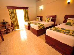 A bed or beds in a room at Hotel & Casino Flamboyan