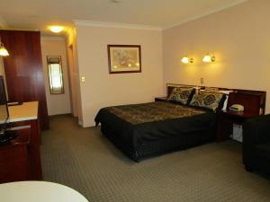 A bed or beds in a room at Southern Comfort Motor Inn