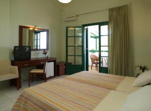 A bed or beds in a room at Skiathos Club Hotel & Suites