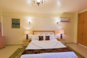 A bed or beds in a room at Maroko Bayshore Suites