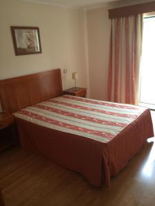 A bed or beds in a room at Residencial São José e Residencial Águas Santas