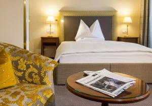 A bed or beds in a room at Parkhotel Graz - Traditional Luxury