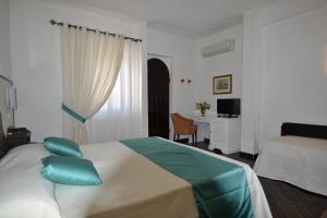 A bed or beds in a room at Hotel Cala di Mola