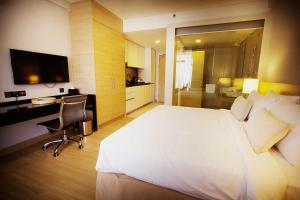 A bed or beds in a room at The Straits Hotel & Suites