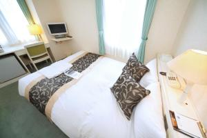 A bed or beds in a room at Hotel Chatelet Inn Kyoto