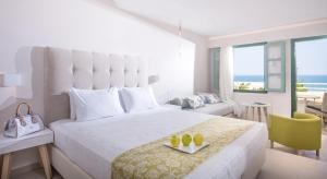 A bed or beds in a room at Petra Beach Hotel