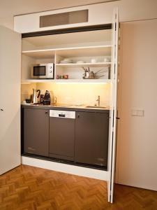A kitchen or kitchenette at CORTIINA Hotel