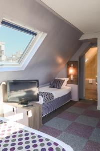 A bed or beds in a room at Comfort Hotel Nation Père Lachaise