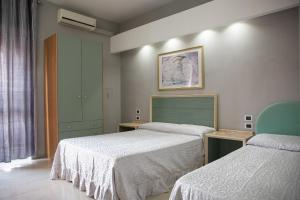 A bed or beds in a room at Maximo Hotel