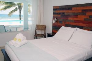 A bed or beds in a room at Bravo Beach Hotel