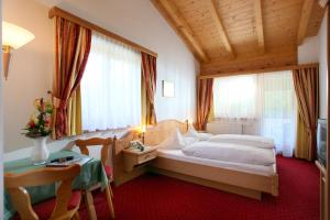 A bed or beds in a room at Alpenhotel Landhaus Küchl