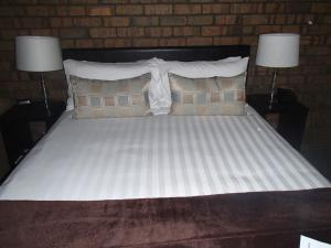 A bed or beds in a room at City Colonial Motor Inn
