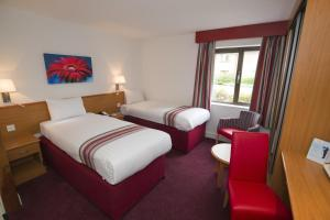 A bed or beds in a room at Ramada Cambridge