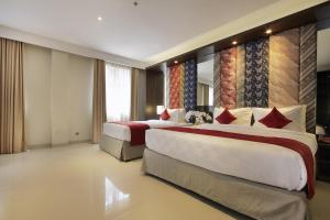 A bed or beds in a room at Ohana Hotel Kuta