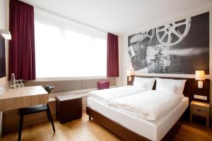A bed or beds in a room at Vienna House Easy München