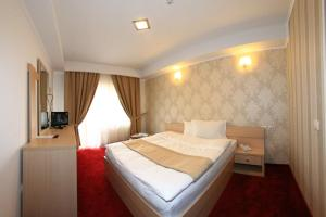 A bed or beds in a room at Hotel Roman Maramures