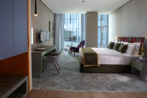 A bed or beds in a room at Ibis Styles Dubai Jumeira