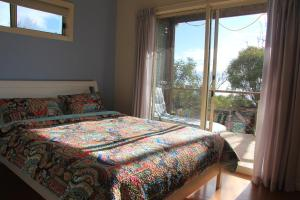 A bed or beds in a room at Emu Bay Stay