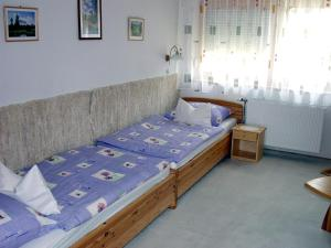 A bed or beds in a room at Lukács Ház