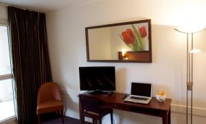 A television and/or entertainment center at Hotel The Originals Boutique Rosny Golf
