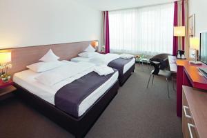 Ein Bett oder Betten in einem Zimmer der Unterkunft Mövenpick Hotel Münster