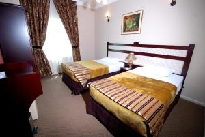 A bed or beds in a room at Al Bustan Tower Hotel Suites