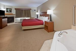 A bed or beds in a room at AmericInn by Wyndham Roseau